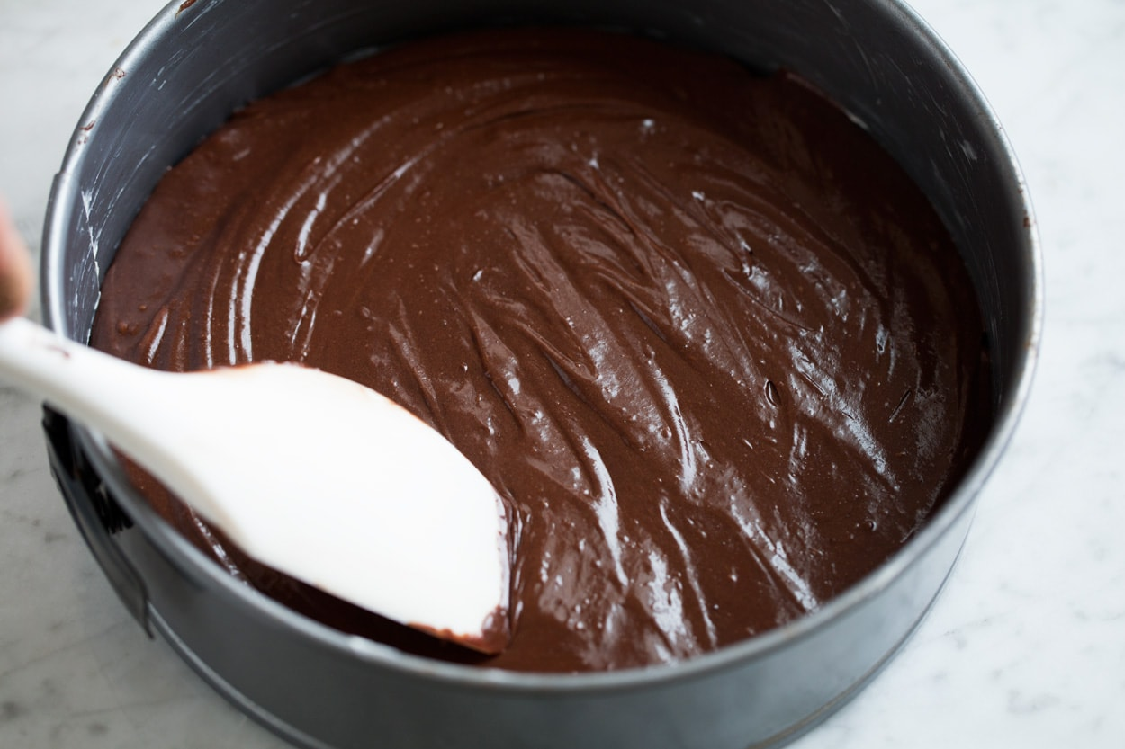 Spreading flourless chocolate cake batter into a 9-inch springform pan.