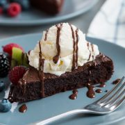 Flourless Chocolate Cake on a blue serving plate. Cake is topped with vanilla ice cream and fudge sauce.