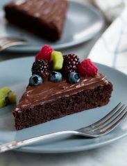 Flourless Chocolate Cake on a blue serving plate. Cake is topped with ganache and fresh fruit.