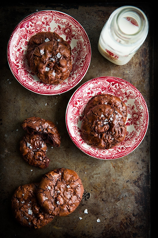 Flourless Chocolate Cookies on red and white plates next to a glass of milk