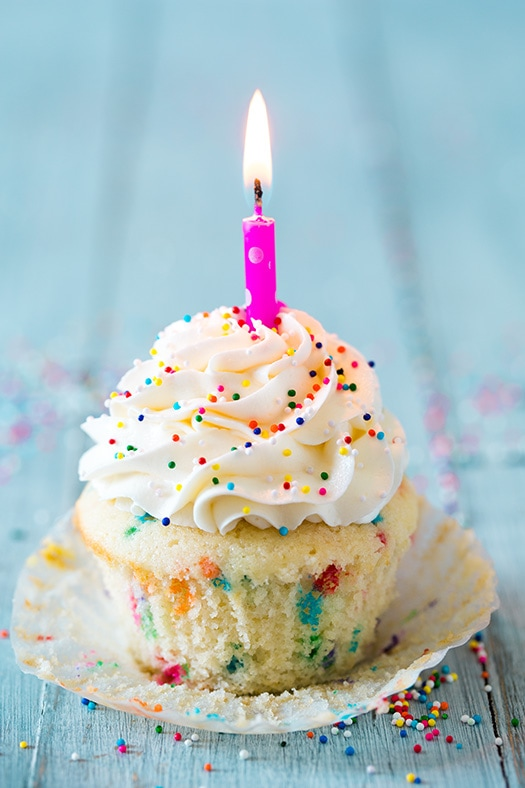 Funfetti Cupcake in paper liner topped with lit birthday candle