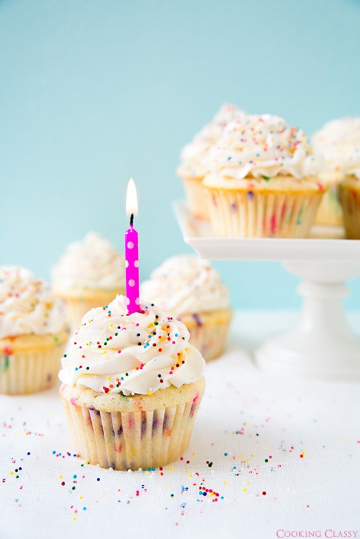 Funfetti Cupcake with lit candle on top and more cupcakes on cake stand in background