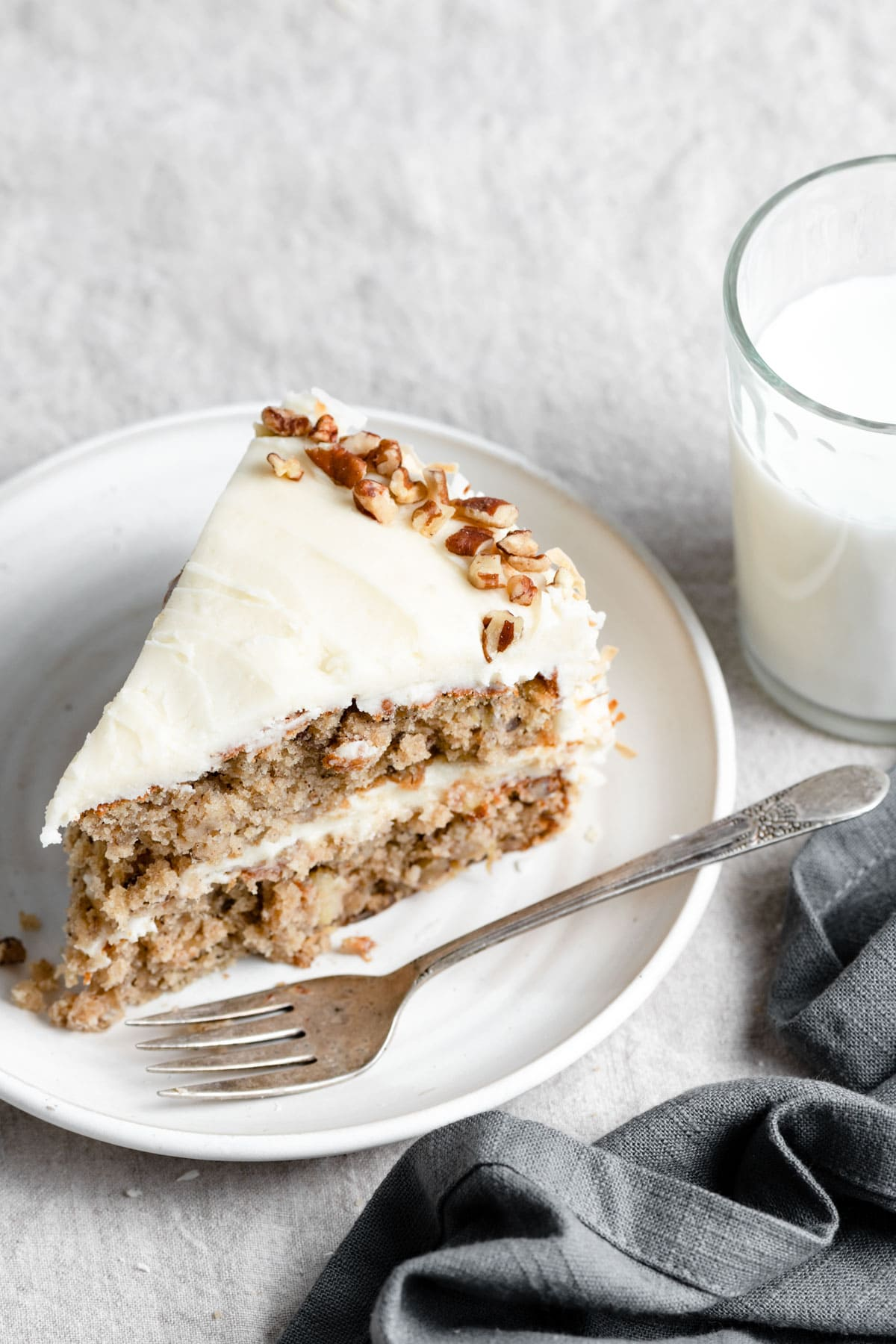 Slice of Hummingbird Cake on a white dessert plate with a fork. Next to they plate there is a dark grey napkin and glass of milk in the background.