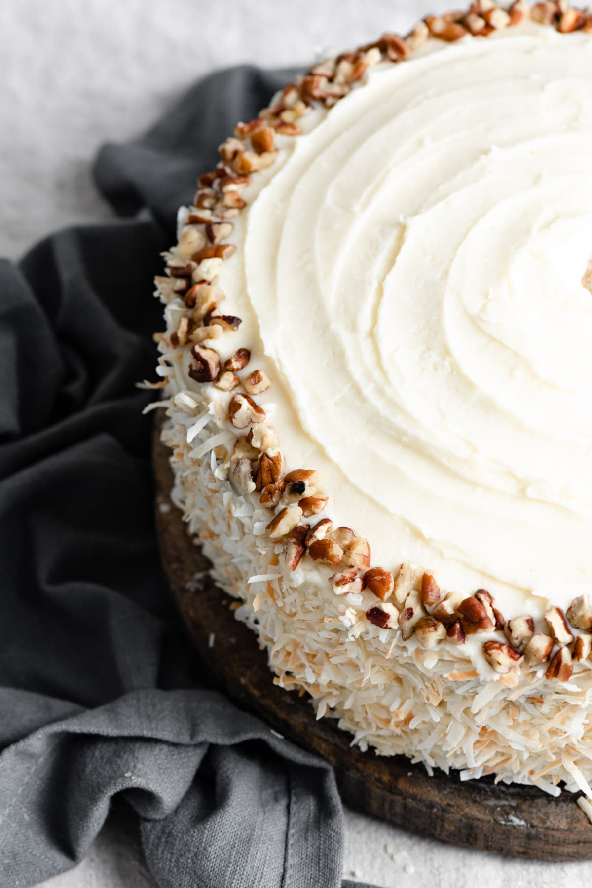 Close up image of whole hummingbird cake showing cream cheese frosting, coconut decorated edges and a ring of pecans on top.