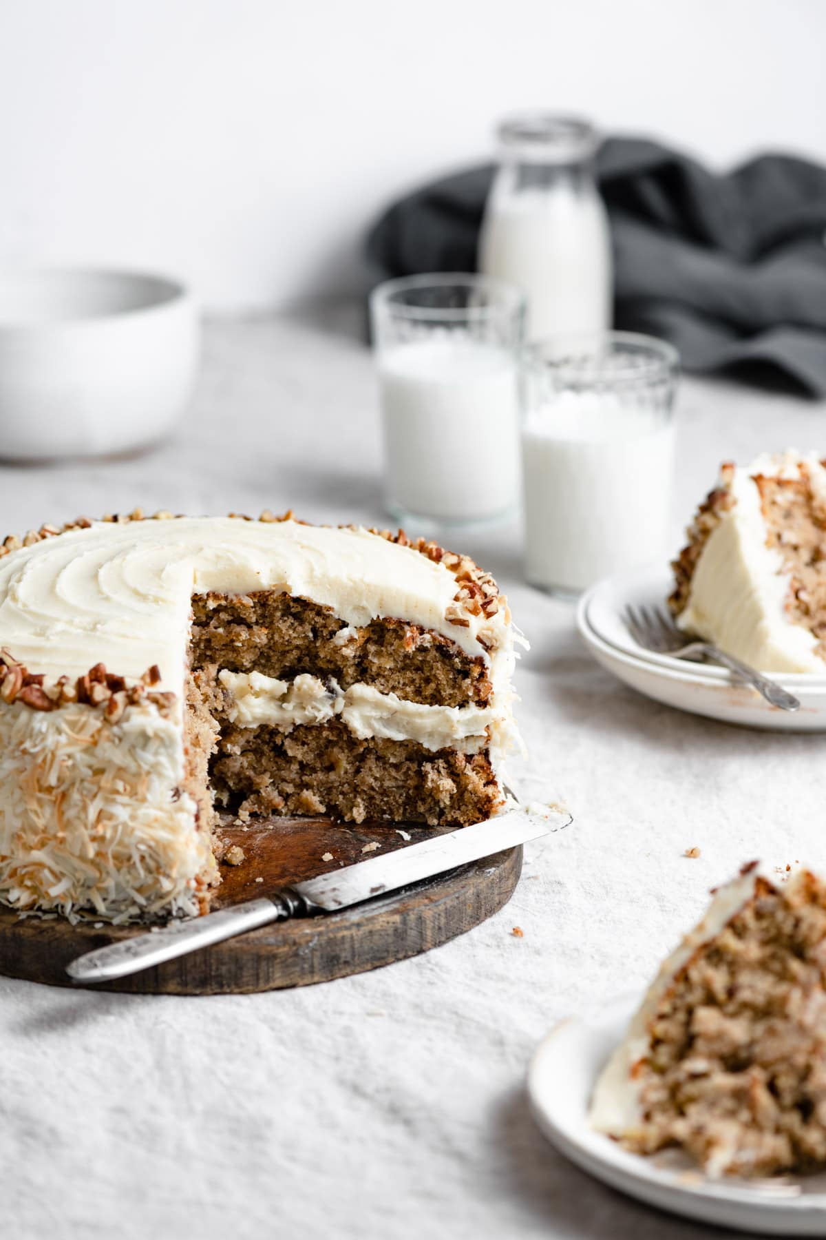 Hummingbird cake shown with a quarter of the cake removed, cake is sitting on a wooden platter. Slices of cake are shown of the the right side.