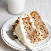 Single slice of homemade hummingbird cake on a white dessert plate.