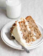 Single slice of homemade hummingbird cake on a white dessert plate.