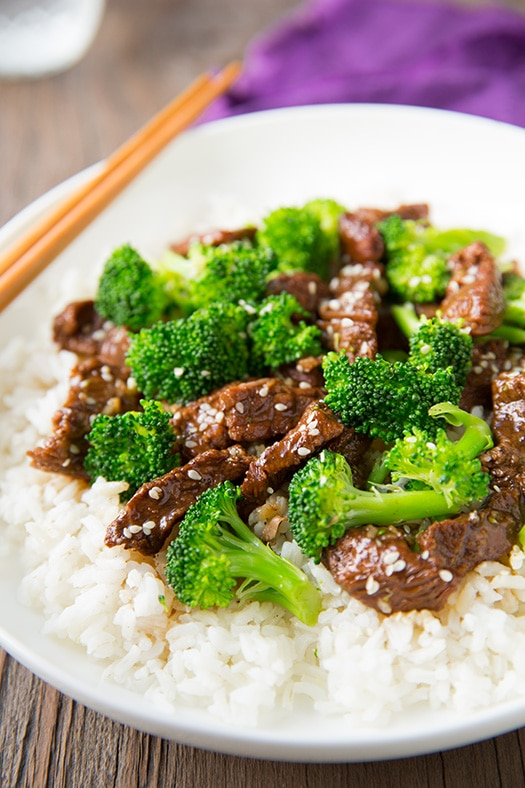 Slow Cooker Beef and Broccoli in white bowl with rice and chopsticks