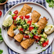 Taquitos on a white plate topped with sour cream, tomatoes, avocados and cilantro. Lime wedges are set of to the side and plate is set on a blue striped napkin.