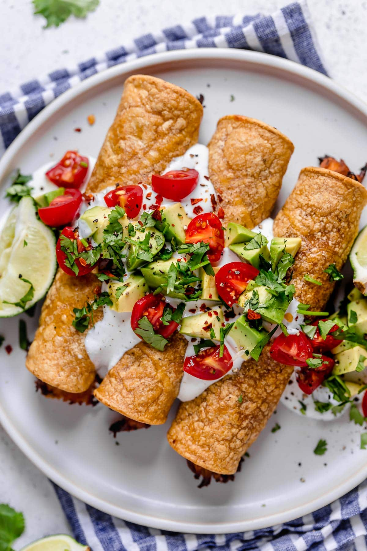 Overhead image of chicken taquitos on a white serving plate topped with sour cream, tomatoes, avocados and cilantro.