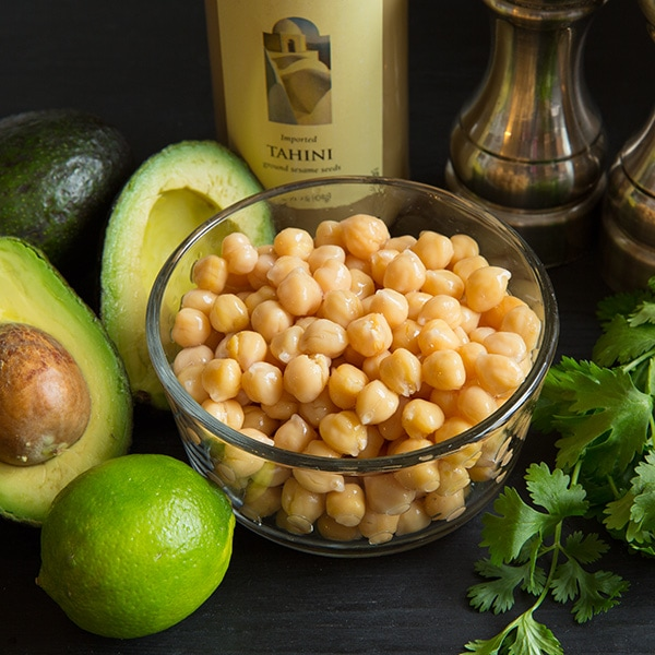 A bowl of chickpeas with other ingredients to make avocado hummus at the side