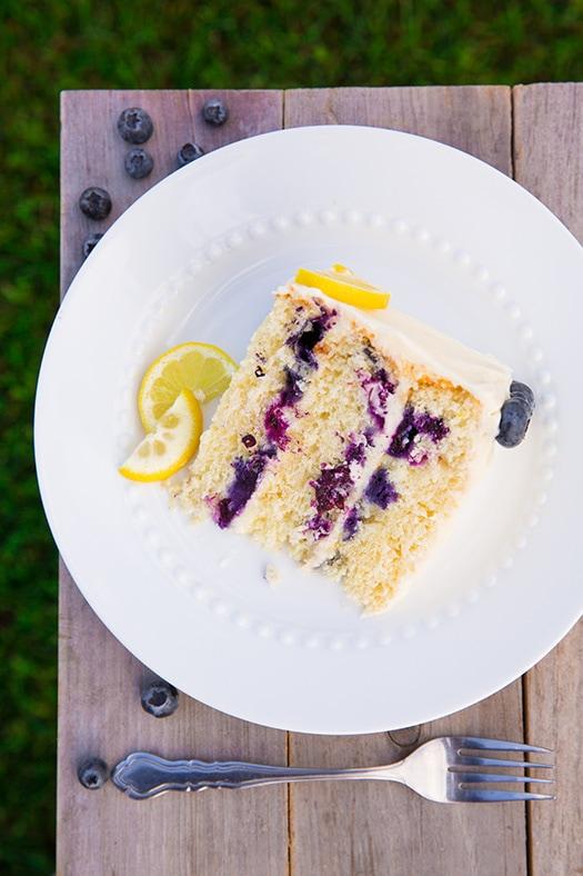 slice of Lemon Blueberry Cake on white plate with lemon slices