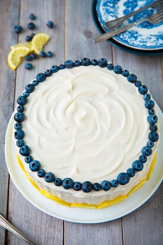 Lemon Blueberry Cake garnished with blueberries and lemon slices on a white plate