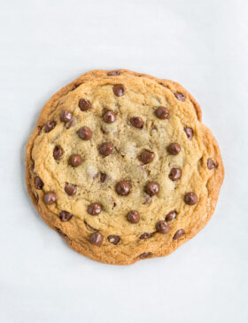 One big chocolate chip cookie shown sitting on white parchment paper.