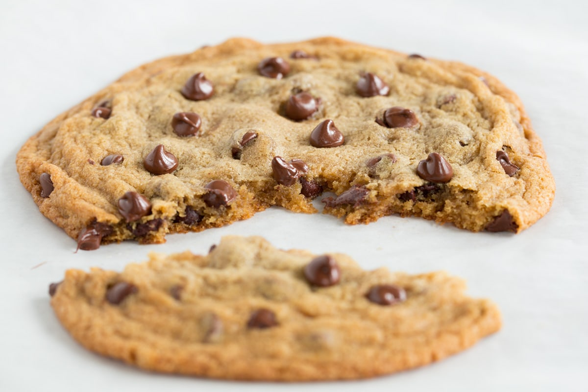 Chocolate chip cookie with a portion broken off to show texture of interior of cookie.