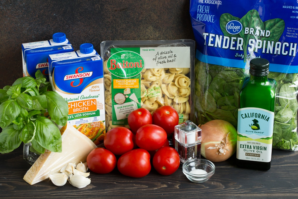 Ingredients needed to make tortellini soup shown here including tortellini, spinach, tomatoes, onion, parmesan, garlic, chicken broth, basil, olive oil.