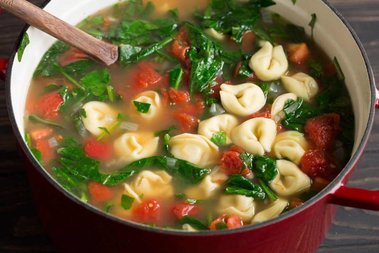 Completed tortellini soup in a large red cast iron pot with a wooden spoon.