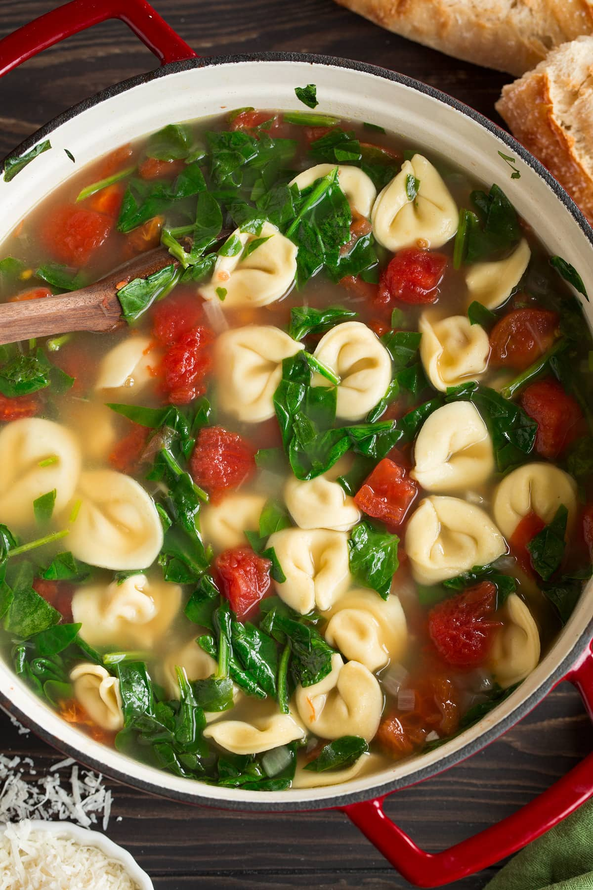 Overhead image of tortellini soup in a large red pot.