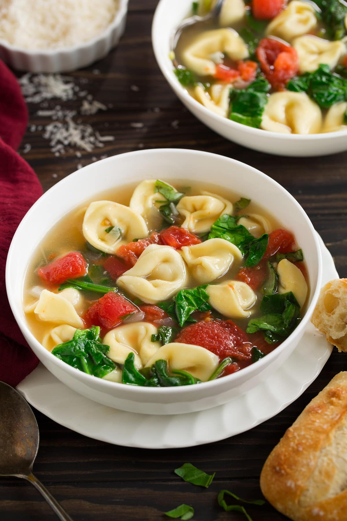Tortellini Soup with Spinach Tomato and Garlic in a white serving bowl set over a ruffled white plate, sitting on a dark wooden tabletop with a side of bread.