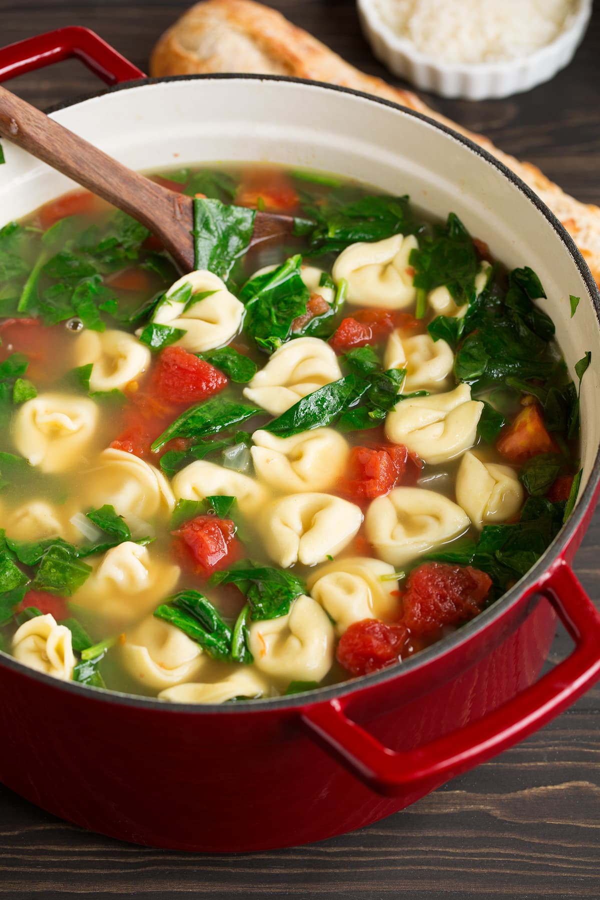 Close up image of tortellini soup in a red pot set over a wooden tabletop.