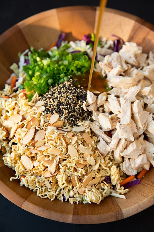 pouring dressing onto Asian Ramen Salad