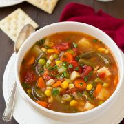 Vegetable soup in a white bowl with crackers in the background