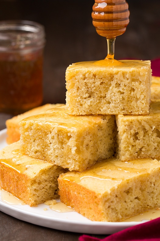 Drizzling honey on a stack of cornbread on a white serving plate set over a wooden table.