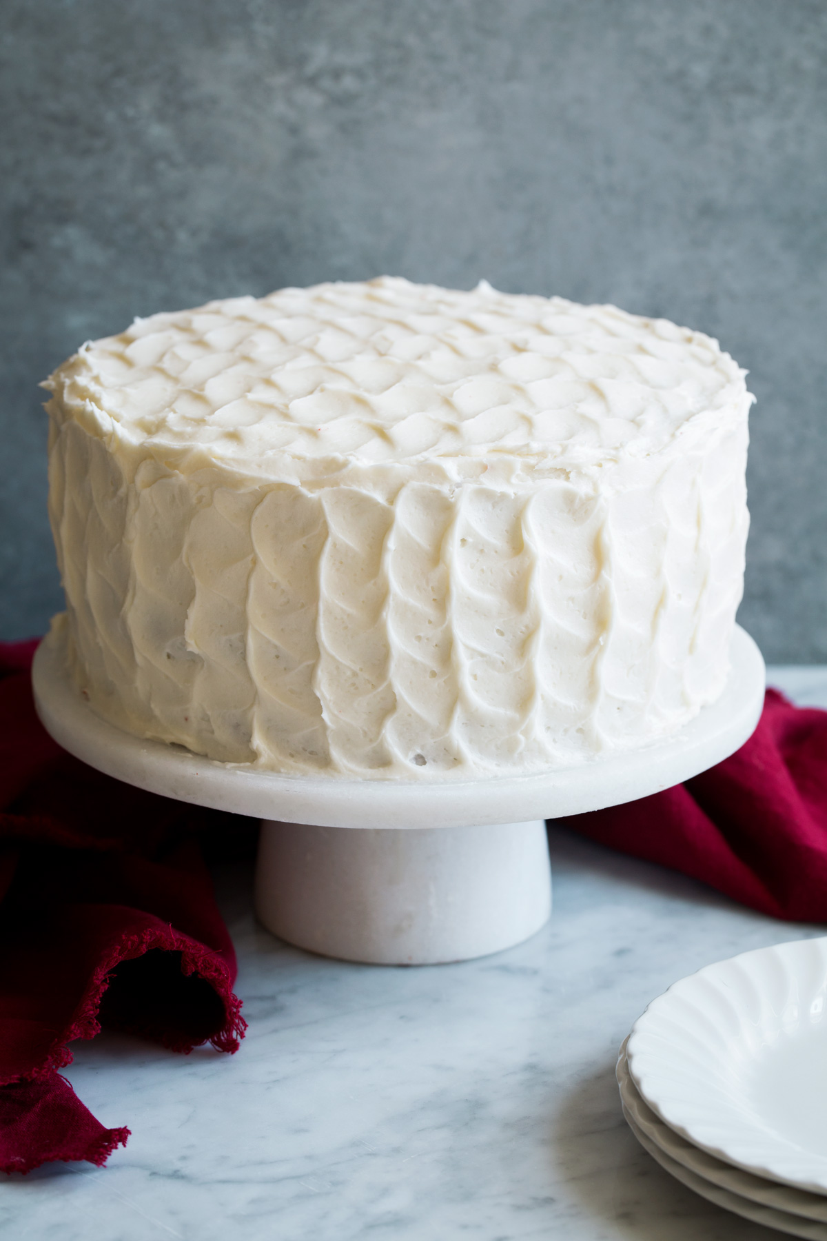 Whole red velvet cake covered in cream cheese frosting with a ruffled design. Cake is sitting on a marble cake stand.