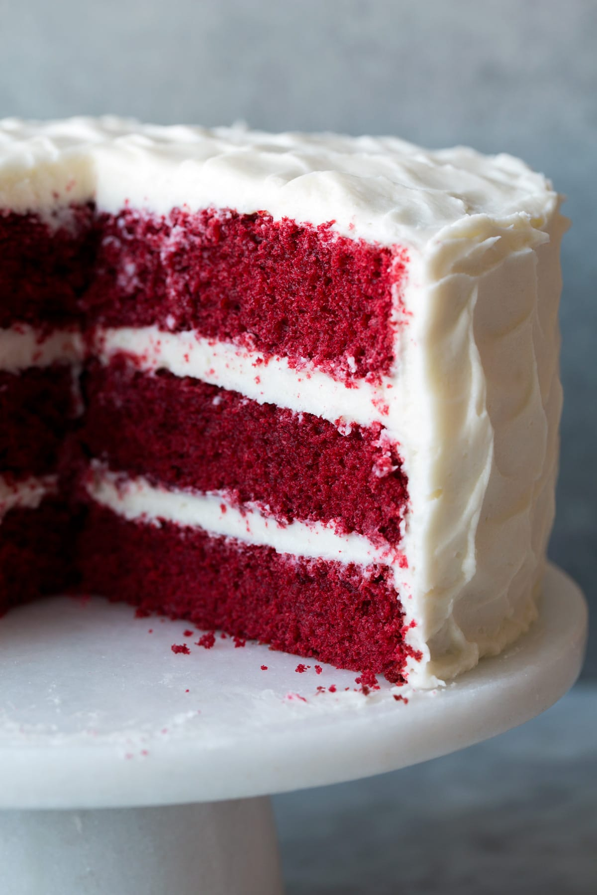 Red Velvet cake with a slice removed to show interior of cake. Cake is resting on a cake stand.
