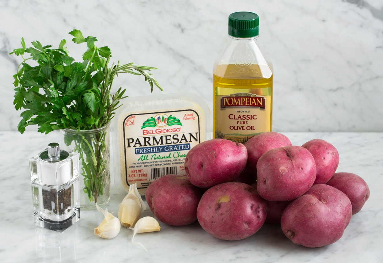 Ingredients needed for roasted potatoes shown here including red potatoes, olive oil, parmesan, garlic, herbs, salt and pepper.