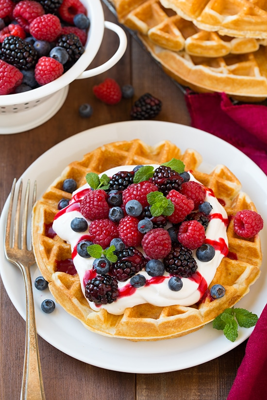 Lightly browned Belgian Waffles topped with cream, berries and garnished with mint
