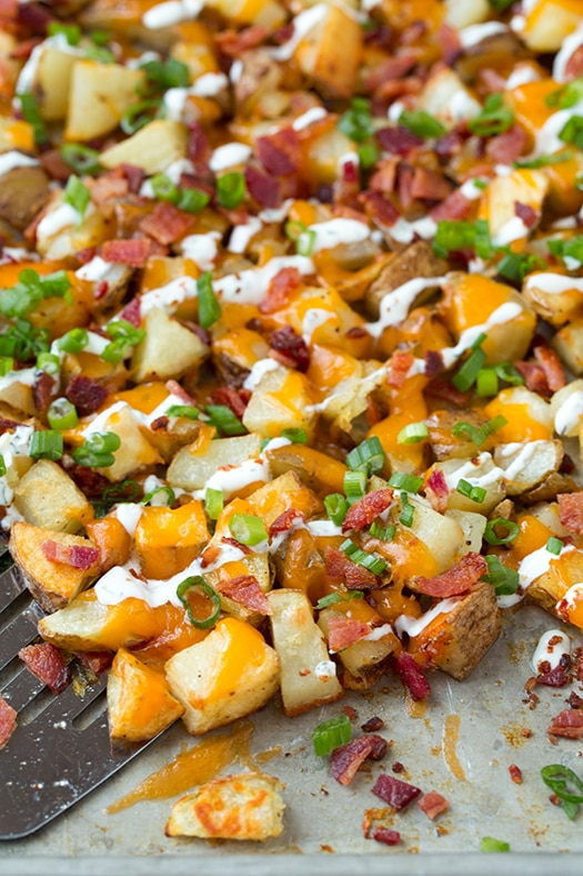 Image of spatula scooping up cheesy potatoes with bacon and ranch.