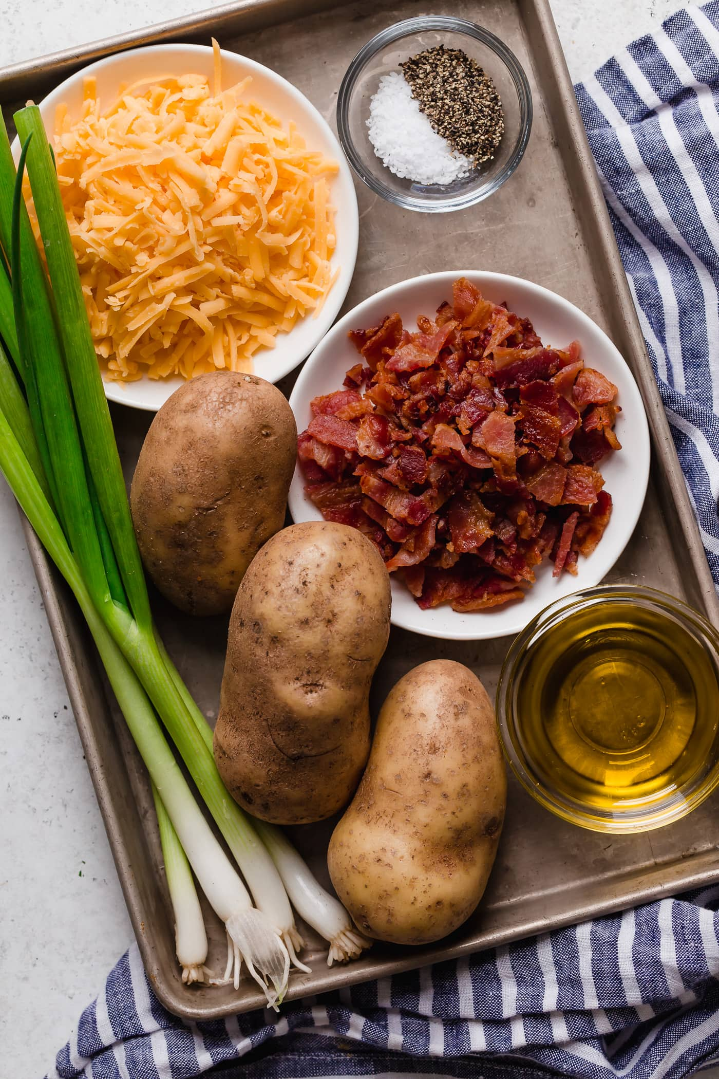 Ingredients needed to make cheesy potatoes shown here including potatoes, bacon, cheddar cheese, olive oil, seasoning.