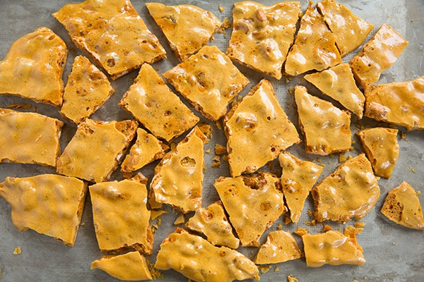 Breaking peanut brittle into pieces after cooling.
