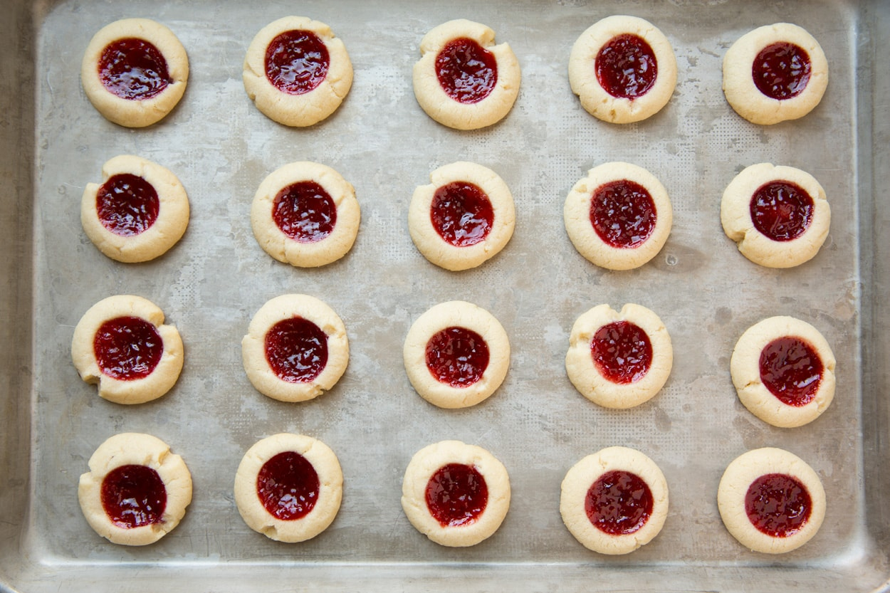 Thumbprint cookies after baking on baking sheet. Showing them spread into nice rounds and jam in center is set.