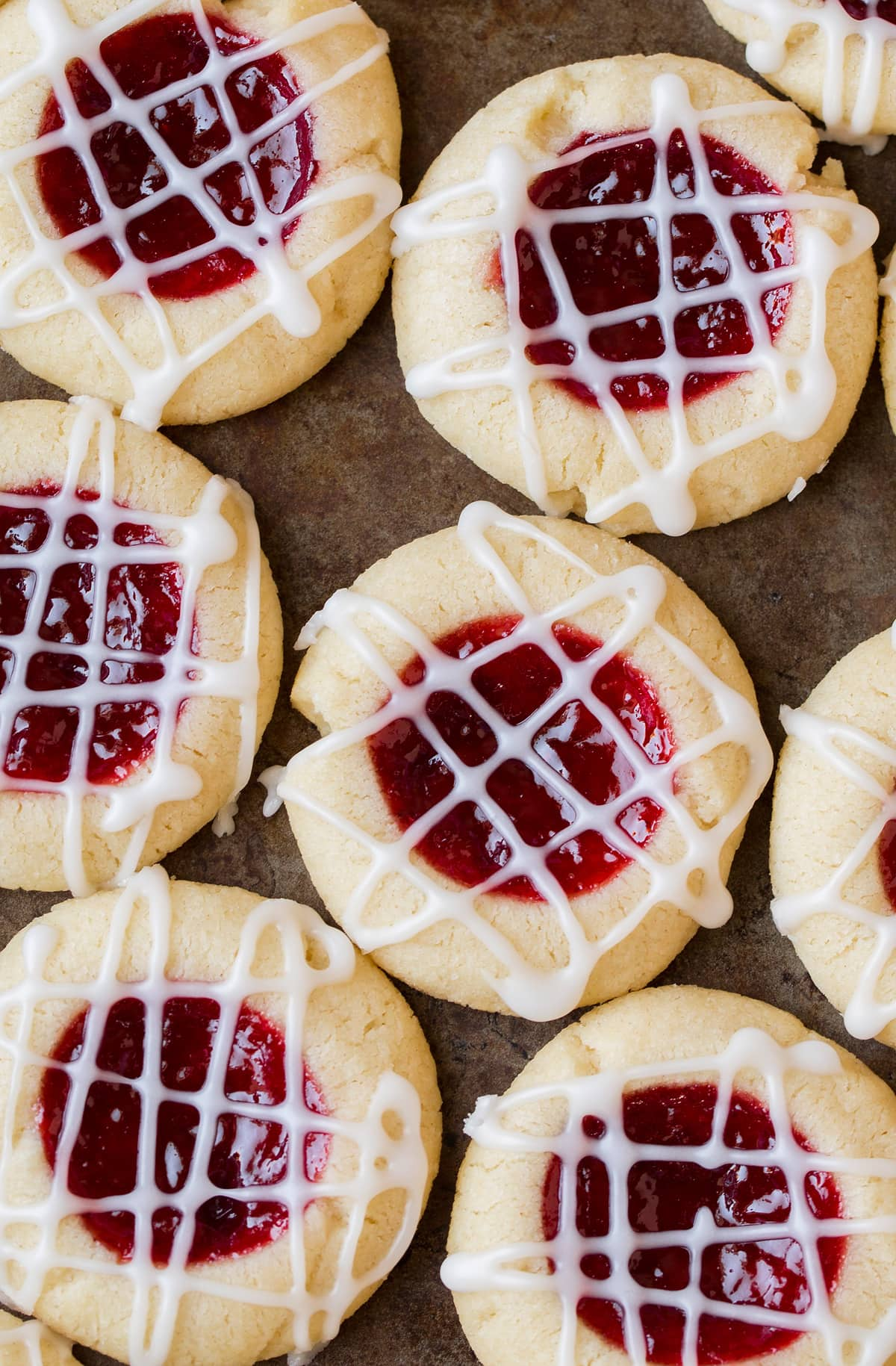 Thumbprint cookies close up image. Cookies are made with a shortbread cookie base and filled with a round of raspberry jam and drizzled with a criss cross pattern of almond glaze.