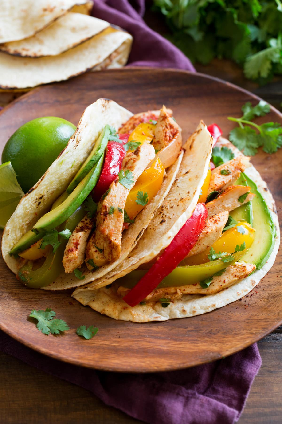 Two chicken fajitas on a wooden plate.