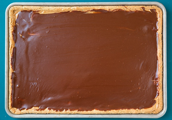Adding chocolate frosting to peanut butter bars.