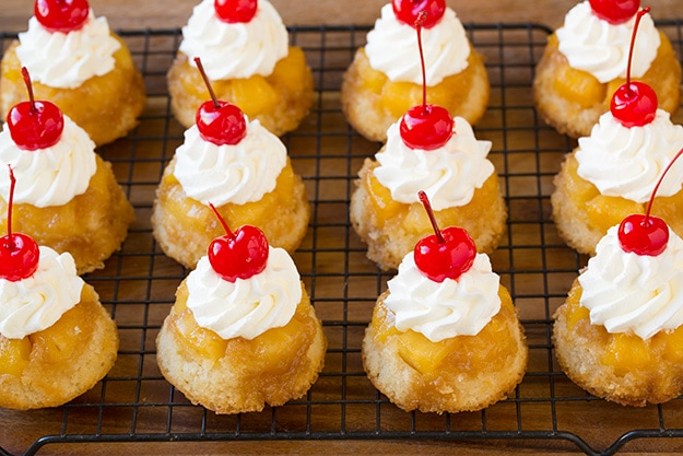 Adding Whipped Cream and Cherry To Pineapple Upside Down Cupcakes
