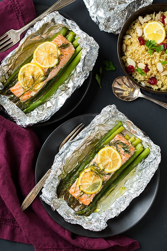 Two plates of Salmon and Asparagus in Foil topped with lemon wedges