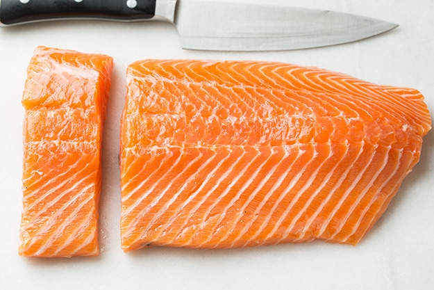 Cutting a side of salmon into fillets.