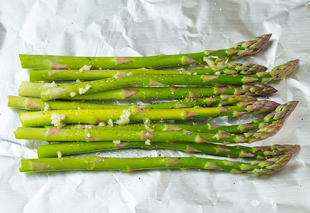 Laying asparagus on sheet of foil before topping with salmon.