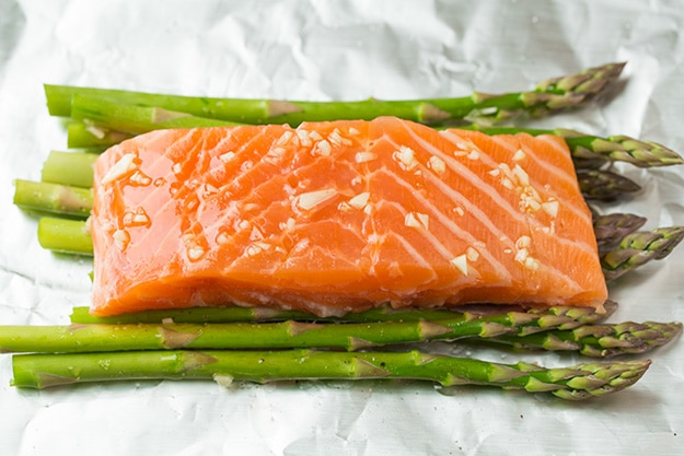 Laying salmon over asparagus on sheet of foil.