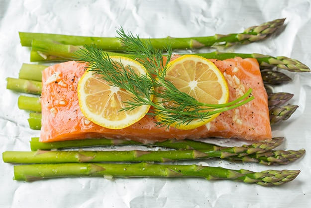 Adding lemon slices and fresh dill over salmon fillet.