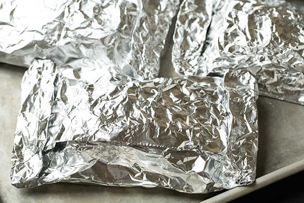 Wrapping salmon in foil packets and setting on baking sheet to bake.