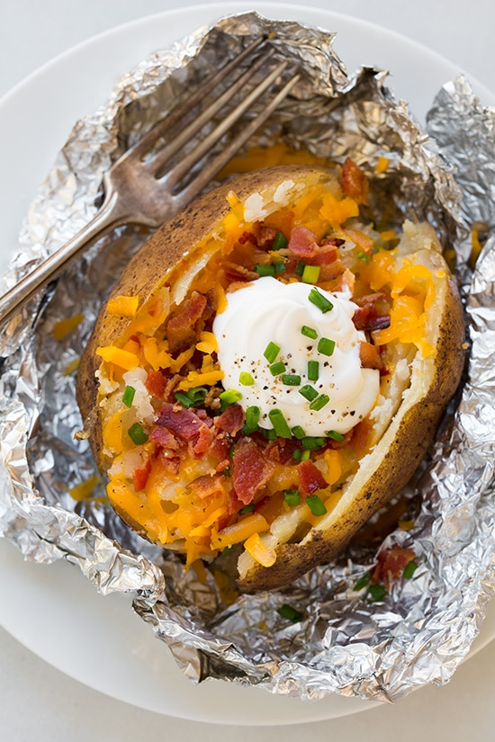 Baked potato made in the slow cooker. Its cut open and topped with cheddar, bacon, sour cream and chives. Overhead image.
