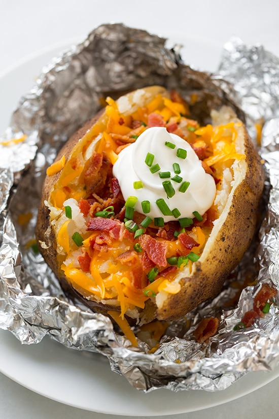 Baked potato made in the slow cooker. Its cut open and topped with cheddar, bacon, sour cream and chives. Shown sitting on a white serving plate.