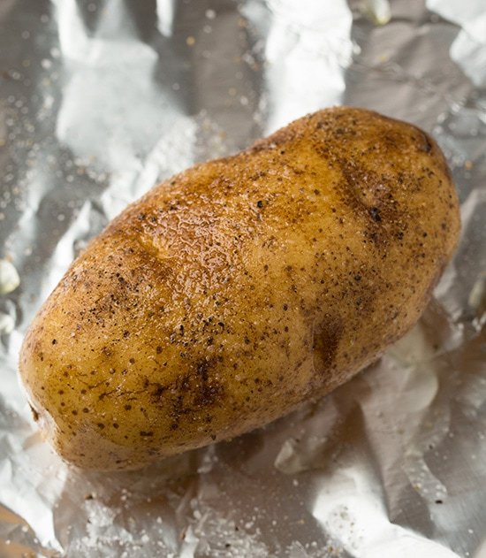 Brushing potatoes with oil and seasoning with salt and pepper.