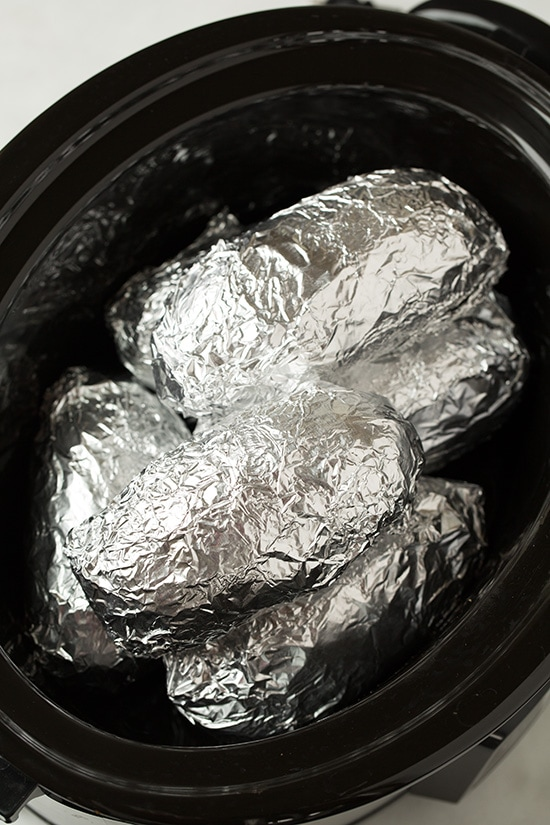 Potatoes wrapped in foil in slow cooker.