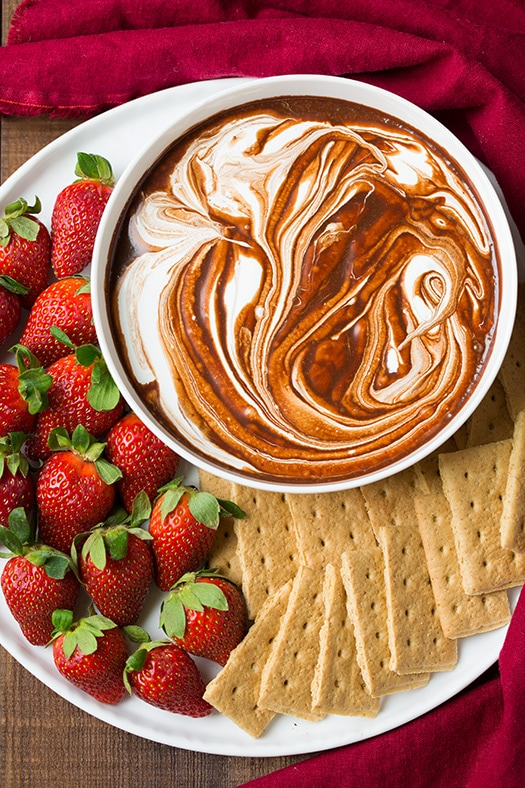 bowl of s'mores dip on platter with strawberries and graham crackers